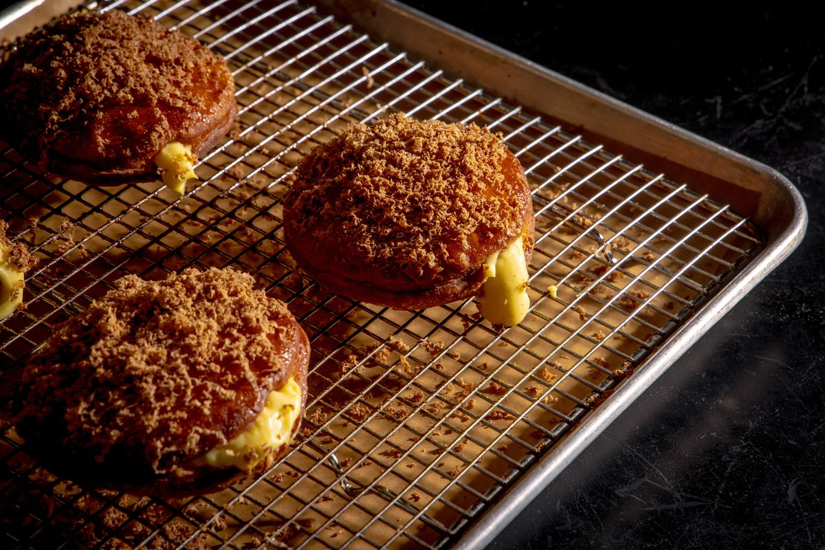Banoffee doughnuts with chocolate hazelnut sit on a wire rack, shot diagonally from above