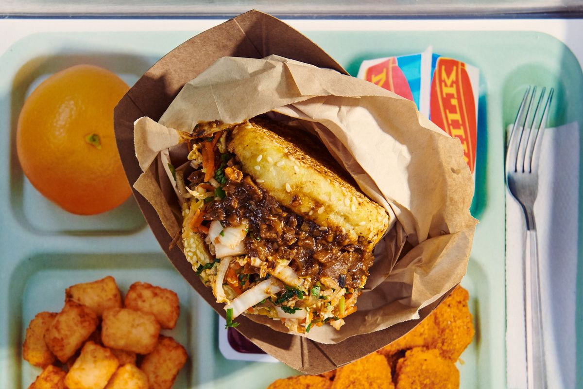 A mushroom sloppy joe sits in a brown plastic wrapper above a lunch tray
