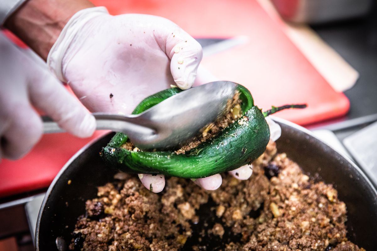 A ground beef mixture being spooned into a green pepper.