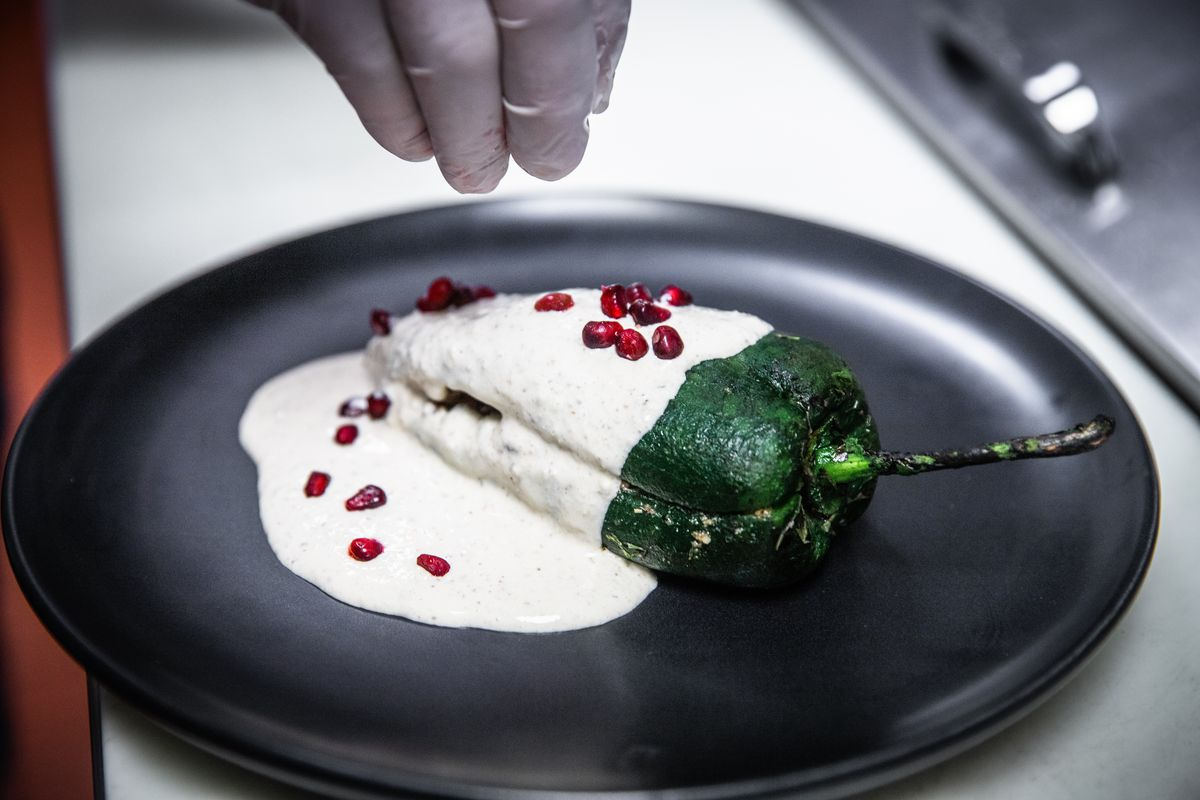 Pomegranate being sprinkled on a green pepper smothered with a cream sauce.